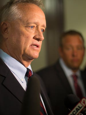 Hamilton County Prosecutor Joe Deters talks to the media as his brother, Commissioner Dennis Deters, looks on.