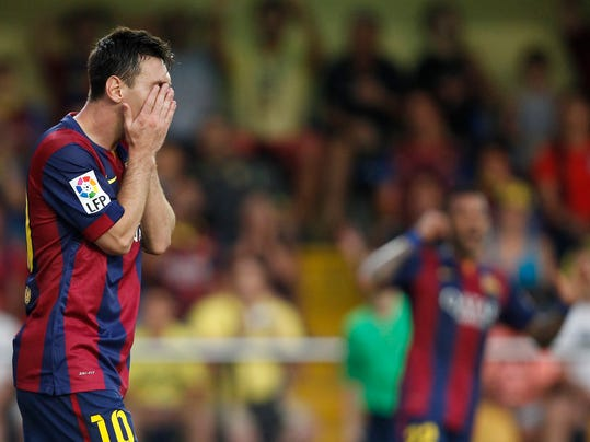 Barcelona's Lionel Messi, from Argentina, covers his face after failing to score against Villarreal during a Spanish La Liga soccer match at the Madrigal stadium in Villarreal, Spain, on Sunday, Aug 31, 2014.(AP Photo/Alberto Saiz)
