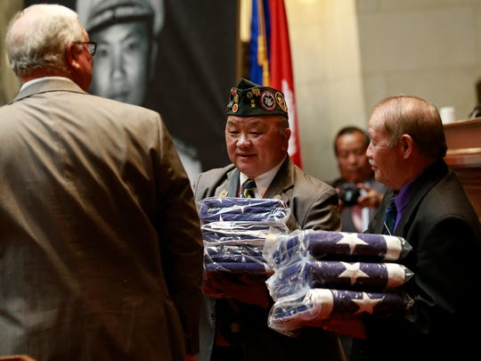 Wisconsin Lao Veterans of America members Zablong Vang, right, and Nao Shoua Xiong, receive some American flags Monday, May 14, 2018, during the Hmong-Lao Veterans Appreciation Day at the state Capitol in Madison, Wis.