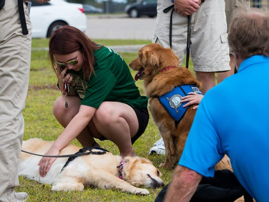A Santa Fe High School student pets a comfort dog at the makeshift memorial outside the school during a moment of silence at 10 a.m. on Monday, May 21, 2018. On Friday, 10 people where killed at Santa Fe High School.