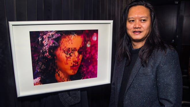 "Artist Rembrandt Quiballo poses with his work, ""Pop Artifact"", an inkjet print on archival paper, at the Sanctuary Camelback Mountain Resort and Spa, Thursday, February 15, 2018.  Quiballo has an exhibit as part of the artist in residence program at the resort."