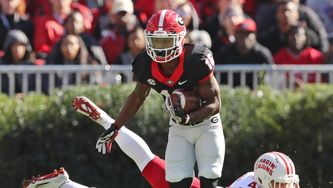 Georgia wide receiver Isaiah McKenzie breaks away from Louisiana-LaFayette defender Stephen Morella returning a punt for a touchdown during the first quarter of an NCAA college football game on Saturday, Nov. 19, 2016, in Athens.