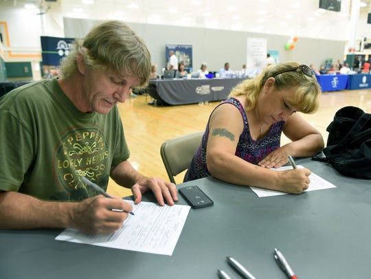 Troy and Melissa Keith fill out applications during