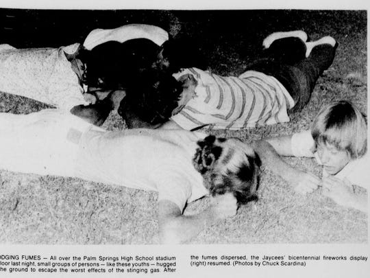 Dodging Fumes: All over the Palm Springs High School stadium floor last night, small groups of persons - like these youths - hugged the ground to escape the worst effects of the stinging gas. Photo by Chuck Scardina appeared in the July 5, 1976, edition of The Desert Sun.