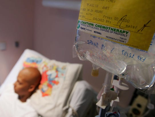 A cancer patient lies in his hospital bed while receiving