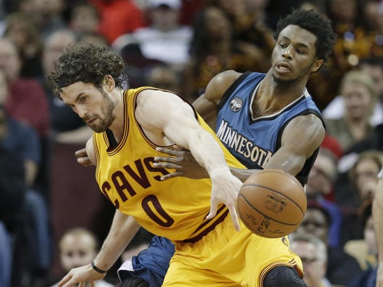 The Minnesota Timberwolves' Andrew Wiggins, right, knocks the ball loose from the Cleveland Cavaliers' Kevin Love in the second half Monday in Cleveland. The Cavaliers won 114-107.