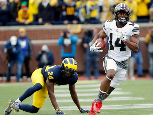 OSU's K.J. Hill runs past U-M's Lavert Hill during the 2nd half at Michigan Stadium in 2017. U-M jumped out to a 14-0 lead but lost 31-20.