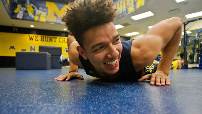 Michigan forward D.J. Wilson stretches out on the mats before a practice session at the Crisler Center in Ann Arbor on Oct. 2, 2015.