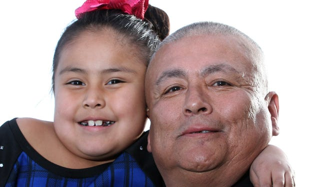 """Andrew """"Boddie"""" Harvey, the voice of Marlin in the Navajo-language version of """"Finding Nemo,"""" poses with his daughter Gianna, who was the voice of one of the baby turtles in the animated film, on Wednesday at the Animas 10 theater."""