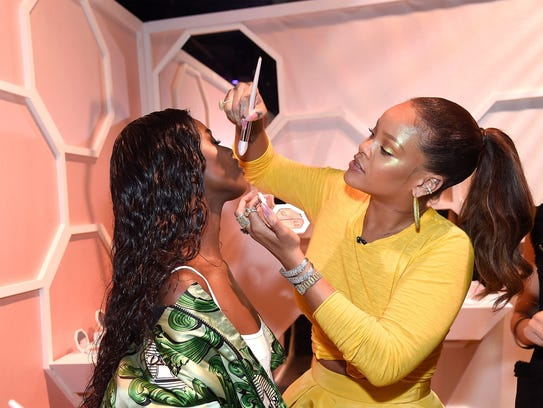 Rihanna helps a fan apply makeup at the launch of Fenty