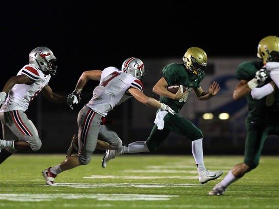 West High quarterback Evan Flitz evades City High defenders