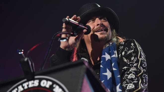 "Kid Rock gives a speech behind a ""United States of 'Merica"" podium at his Little Caesars Arena show in Detroit on Tuesday, Sept. 12, 2017."