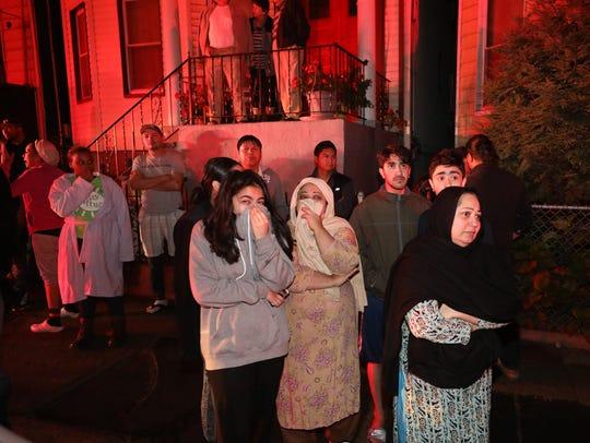 Neighbors watch from across the street as a 4-alarm fire tears through adjoining buildings on Oak Street in Yonkers.