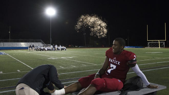 Fireworks explode in the distance as Natick High athletic trainer Lindsay Twohig takes tape off Terrance Cherry's ankle after the Redhawks defeated the Rockets of Needham High pm Sept. 6, 2019. Twohig is one of many local athletic trainers who have had to adapt this year during the COVID-19 pandemic.