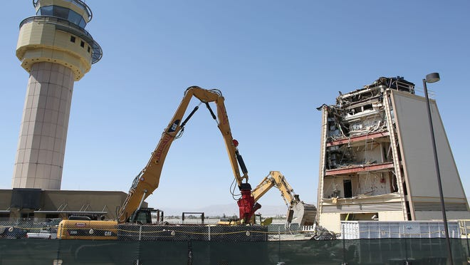 Construction crews tear down the old airport tower at Palm Springs International Airport Monday, June 9, 2014.  At left is the new tower.