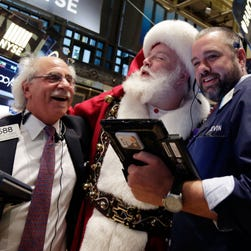 Traders pose Wednesday with Santa Claus on the floor of the New York Stock Exchange.