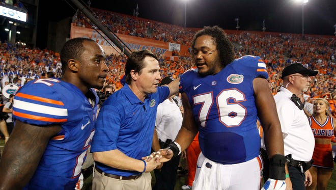 Sep 13, 2014; Gainesville, FL, USA; Florida Gators head coach Will Muschamp, defensive back Jabari Gorman (2) and offensive linesman Max Garcia (76) celebrate after they beat the Kentucky Wildcats in triple overtime at Ben Hill Griffin Stadium. Florida Gators defeated the Kentucky Wildcats 36-30 in triple overtime. Mandatory Credit: Kim Klement-USA TODAY Sports