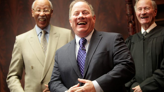 Mike Duggan, center, laughs with former Mayor Dave Bing, left, and his father, Federal Judge Patrick Duggan, after being sworn in as mayor of Detroit on Wednesday, Jan. 1, 2014.