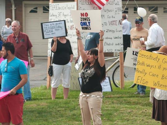 Debbie Rosi (center), organizer and owner of home in background, leads the protest of the construction of a mosque on 15 Mile Road in Sterling Heights, Michigan August 29, 2015.