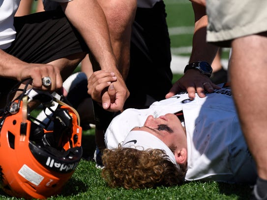 Brother Rice personnel attend injured QB  Mariano Valenti.