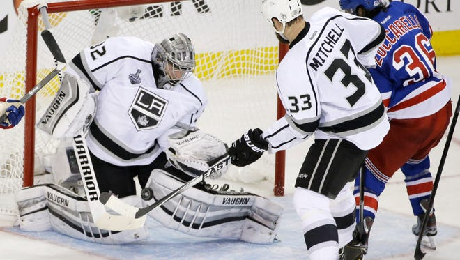 Kings goalie Jonathan Quick blocks a shot by Rangers right wing Mats Zuccarello as Kings defenseman Willie Mitchell helps defend Monday. Los Angeles won 3-0 in Game 3.
