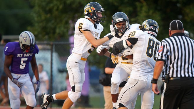 Avon's #3 is congratulated for his long run and touchdown bringing the score Avon to 13, to tie with extra point at 14-14 in the first quarter during the Avon at Ben Davis High School football game, Friday, August 28, 2015.