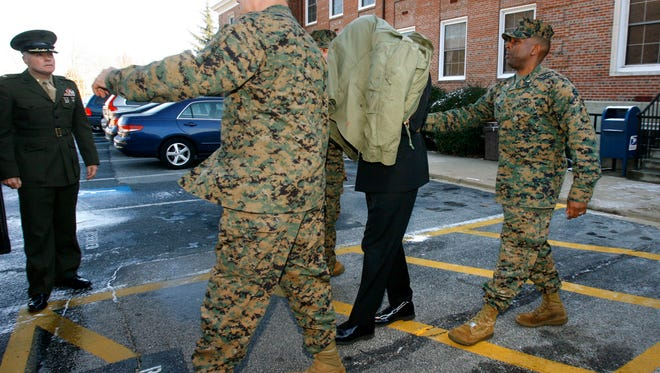 Lt. Cmdr. John Thomas Matthew Lee, 42, (second from right) seen under a jacket, is escorted in shackles from his general court martial at Marine Corps Base Quantico in Quantico, Virginia, on Dec. 6, 2007. A judge once again postponed his sentencing.