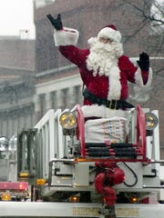 Snowflakes falling and blowing around, Santa Clause waves and throws candy to the crowd as he rides atop a Henderson Fire Department engine bringing up the rear of the Christmas Parade in Downtown Henderson Saturday morning, December 2, 2000. (Gleaner photo by Darrin Phegley)