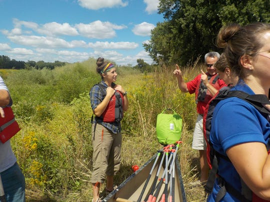 Molly Hanson engages with volunteers during a river cleanup this past summer.