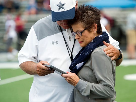 Farragut head coach Eddie Courtney and wife Anita hug after Courtney was presented with the Careacter Star Coach of the Year award before the game against Morristown West at Farragut on Thursday, Aug. 31, 2017.