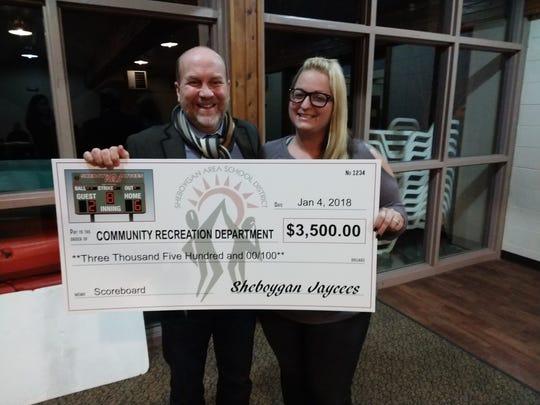 Jenna Van Der Sande, Sheboygan Jaycees treasurer, presents a donation check to Community Recreation  Department Director John Koehler.
