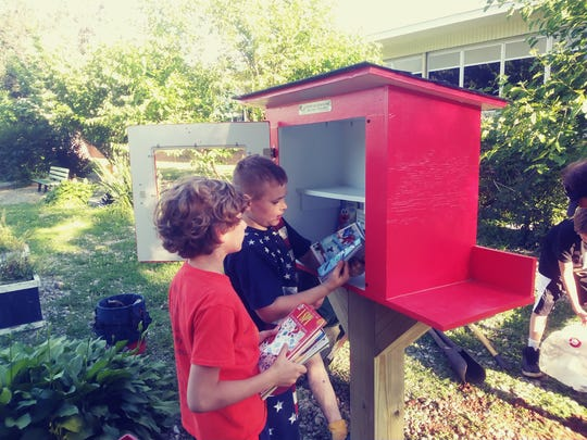 Two members of Cub Scout Pack 64 load up the Free Little Library with their favorite books.
