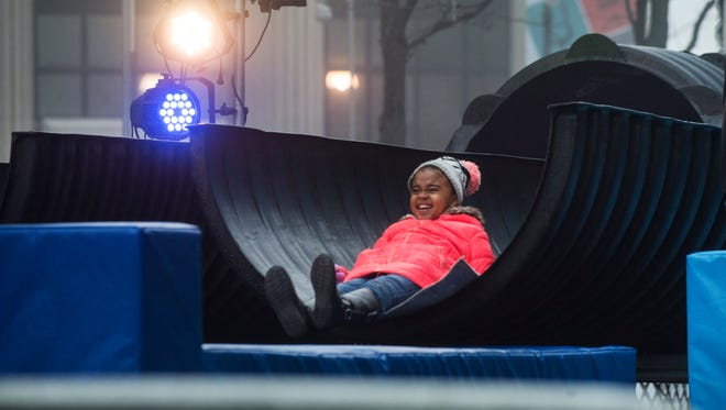 Bailey Buford, 7, of Detroit reaches the bottom of a giant slide at Winter Blast.