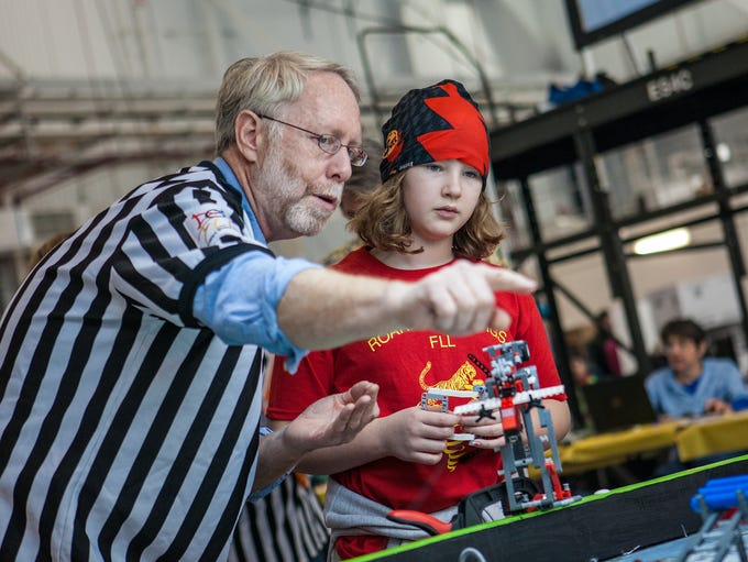 Referee Chris Hyde clarifies a point with Brader Elementary School team member Emma Reilly at the First Lego Tournament held at the Delaware Air National Guard base in New Castle.