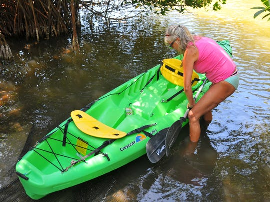 Hollyann Weed with Calypso Kayaking puts a kayak in the Banana River on Wednesday at Ramp Road for a customer.The Banana River water was tested this week over health concerns for participants in this weekend's triathlon where participants will swim in the Banana River.