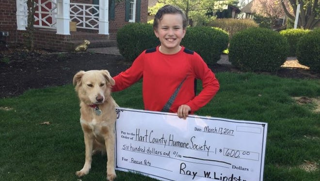 Ray Lindstrom and his rescued canine companion, Abby Rae, show off money donated in honor of Abby Rae's rescue.