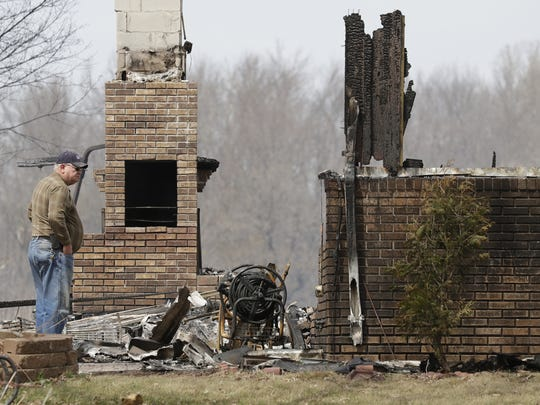 A man looks over a home that was destroyed by fire Tuesday at 3302 Breezewood Lane in Clayton. The remains of two people were found inside.
