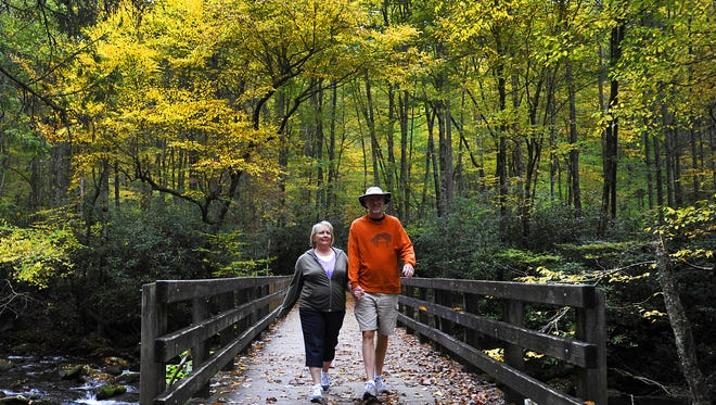 Marla and David Bell from Kingsport, Tenn. walk across the Kephart Prong Trail bridge over the Oconaluftee River in the Great Smoky Mountains National Park.