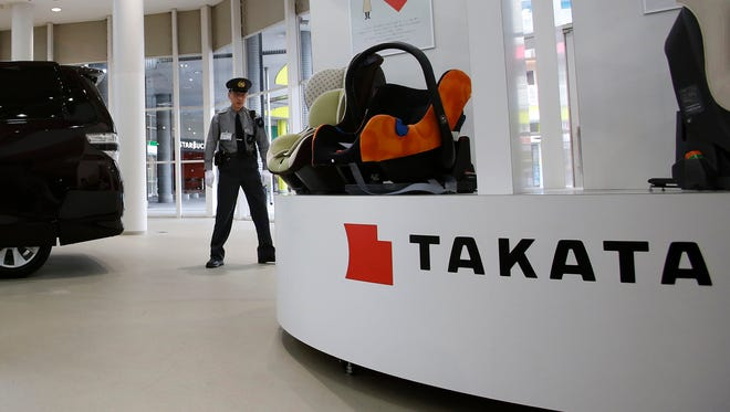 In this Nov. 6 file photo, a security guard stands by child seats, manufactured and displayed by Takata,  at an auto showroom in Tokyo.