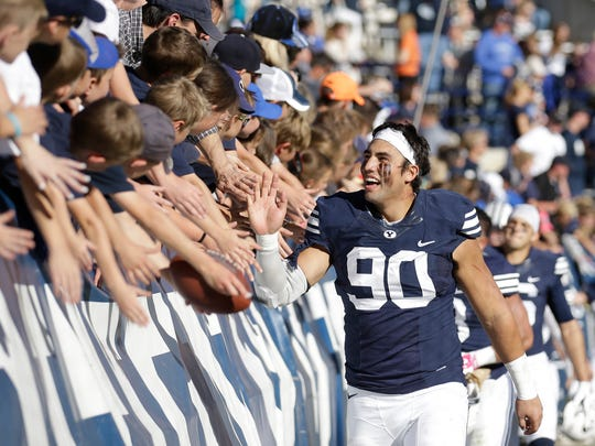 BYU defensive lineman Bronson Kaufusi (90) celebrates with fans following their NCAA college football game against Wagner Saturday, Oct. 24, 2015. BYU won 70-6.