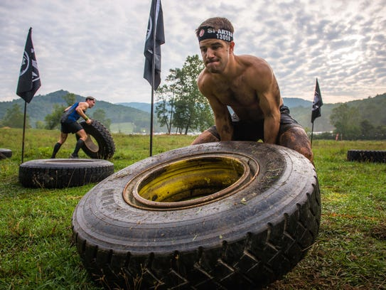 Matthew Zangle tests his might on the tire flip obstacle
