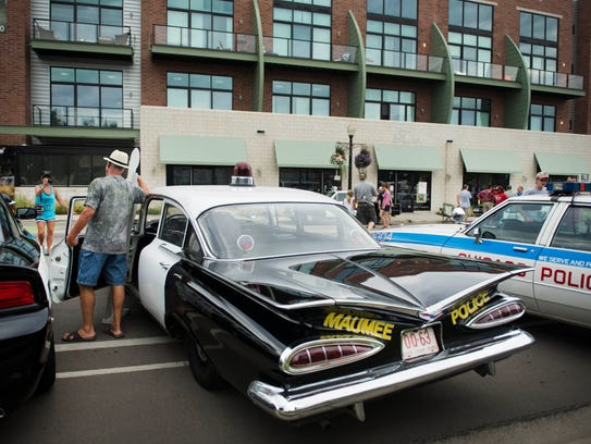 Cruisers take photos with vintage police cars  at the