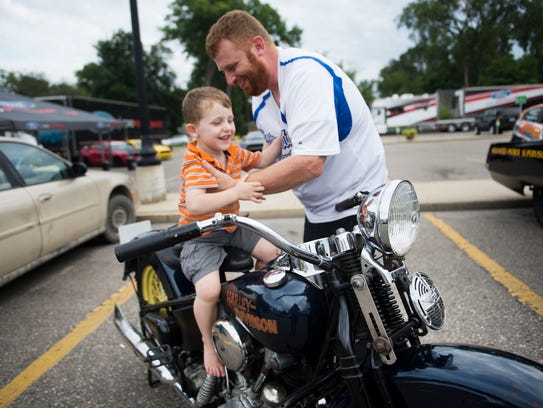 Sgt. Brandon Cole, places his son William, 3, on a