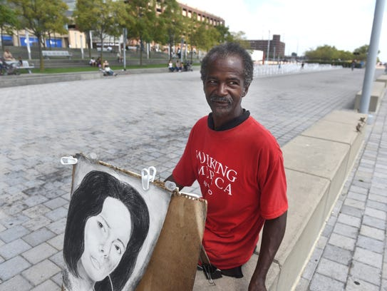 Durk Barton, of Detroit, shows off his artwork along