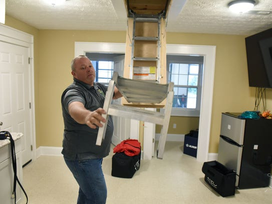 Jason Estes shows off a small model house demonstrating