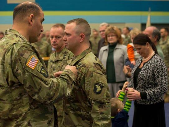 Maj. Gen. Andrew Poppas pins the Soldier's Medal on