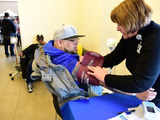Joan Wendolowski, RN, checks the blood pressure of