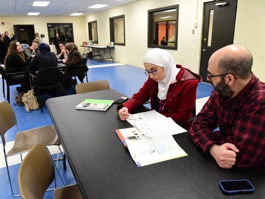 Liza Abdulah learns English with a volunteer, Reid