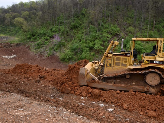 Blount Excavating worker spreads new fill dirt at the