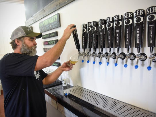 Tom Goebel pours a craft beer from the selection of